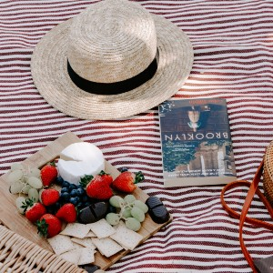 Striped picnic blanket with a straw hat, plate of fruit, cheese and crackers and a book