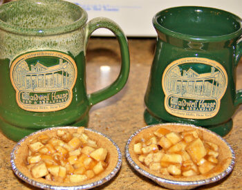 Two green pottery coffee mugs with Caldwell House emblem and two petite individual size apple pies.