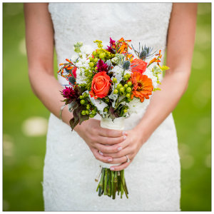 Bride in white wedding dress standing holding a bouquet of flowers with green grass in background