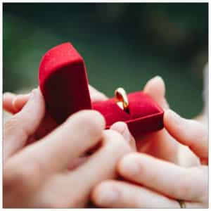 The hands of a couple holding a red velvet ring box open showing a gold ring