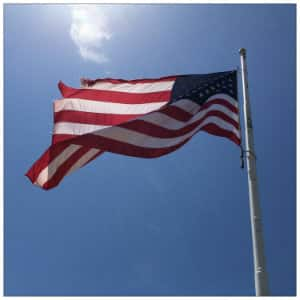 Red, white and blue American flag waving in a bright blue sky