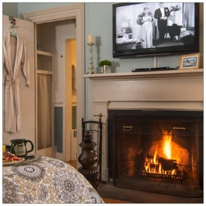 A beautiful room with a fireplace roaring, large screen tv above mantel and luxury robe hanging over the door
