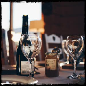 Empty wine glasses on a table next to a bottle of wine with bright window in background - image by quentin-dr-178096 unsplash.com