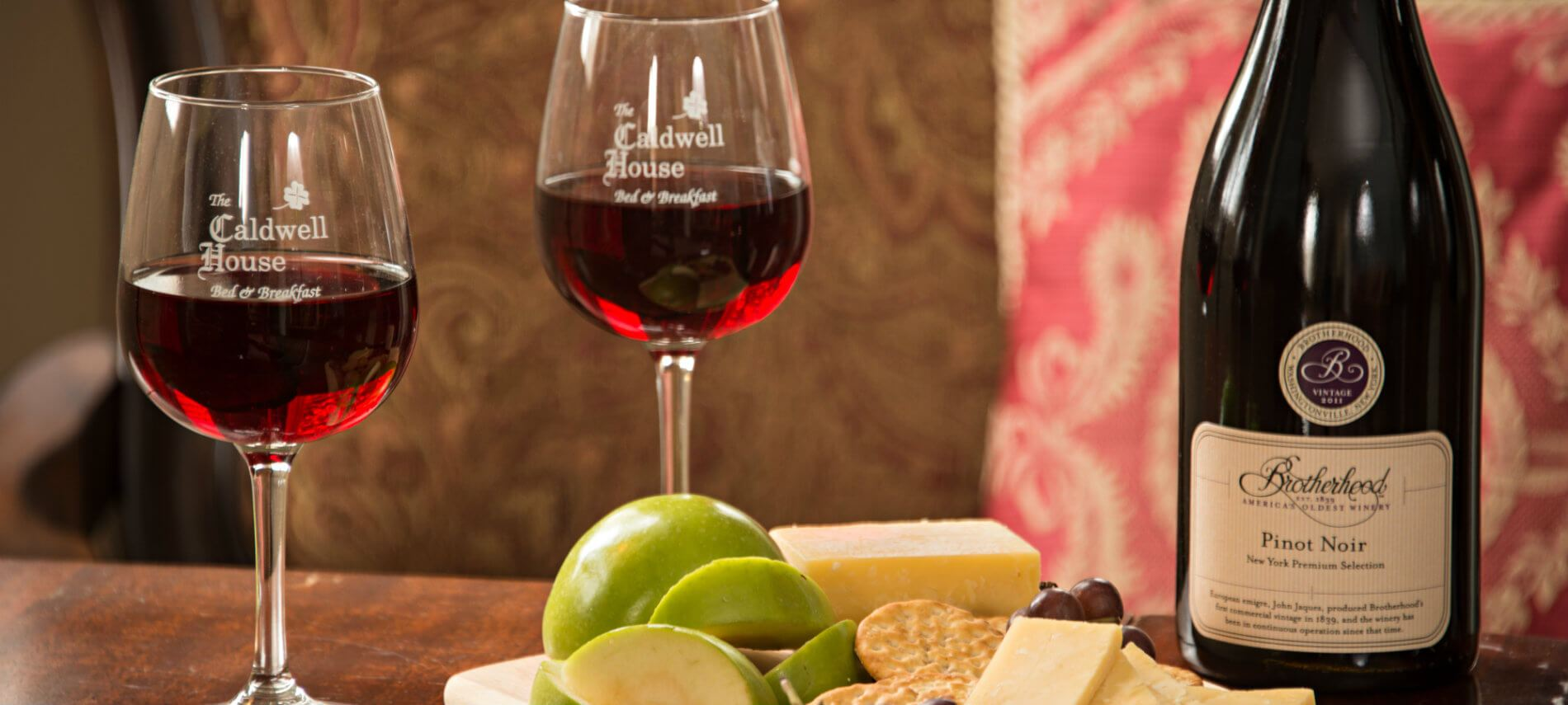 Enticing selection of healthy fruit, cheese, and crackers served with a bottle of Pinot Noir and two wine glasses