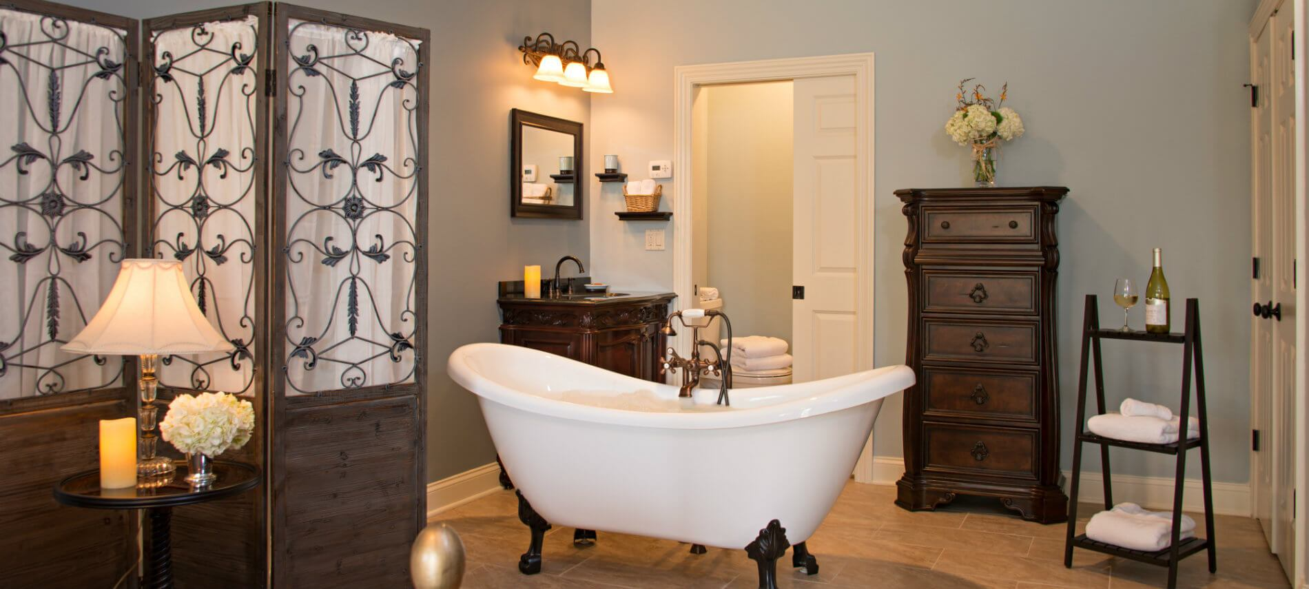 Elegant bathroom with sage blue walls features a white clawfoot bathtub in the center of room with dark wooden furniture