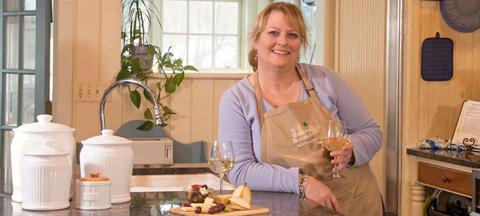 A proud and happy innkeeper smiles as she displays her charming kitchen, a selection of fine foods and wine