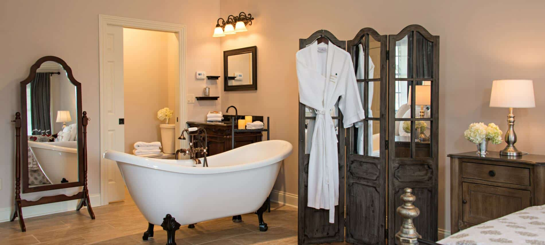 Ensuite within guestroom features white clawfoot bathtub in center of room with spa amenities within reach