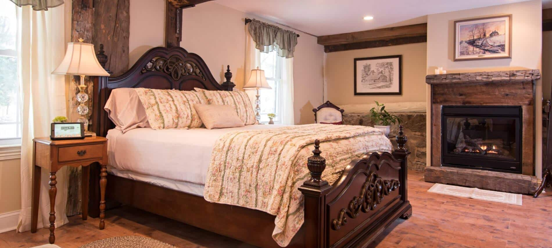 Guestroom features rustic wood fireplace and neatly made bed with white linens and cozy quilt