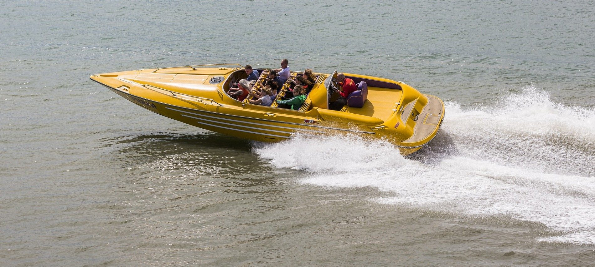Bright yellow powerboat with multiple passengers speeding across an empty body of water with white spray behind