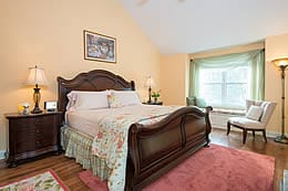 Large cherry wood queen sleigh bed on a rose colored area rug in a room with vaulted ceilings.