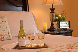 Tray of white wine and two wine glasses on a neatly made bed with lit candles on a dark wood nightstand.