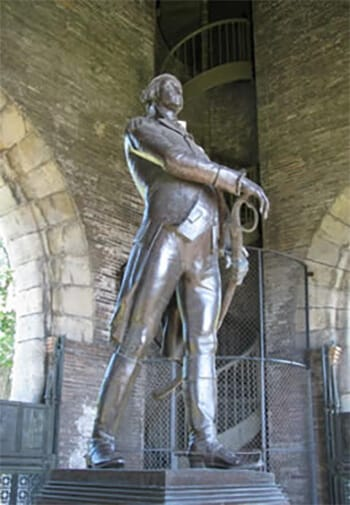 Metal statue of a man drawing his sword surround by a building of golden brick.