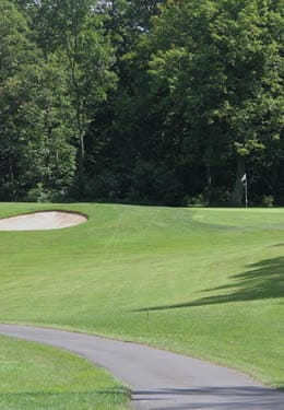 Golf course with groomed greens, a cart path and mature trees in the background.