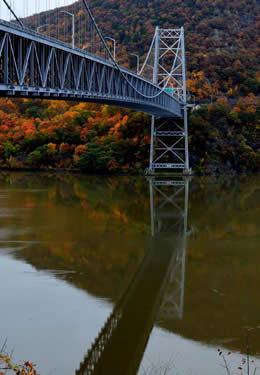 Long bridge over an expansive river with fall trees in the background.