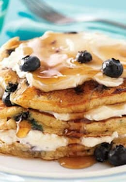 Close up of a stack of pancakes stuffed with cream and blueberries and drizzled in maple syrup.