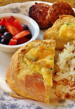 Baked egg and biscuit with shredded hashbrowns and a bowl of fresh berries.