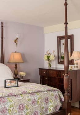 Four poster cherry bed with a lilac floral print quilt and comfortable lounge chair.