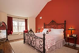 Large queen bed with rought iron headboard against a sienna orange wall, with a window bench seat.