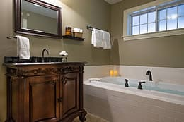 Large soaking tub with candles next to a dark wood cabinet sink and crisp white bath towels.