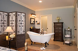 White porcelin clawfoot tub in a large bed and bath area.