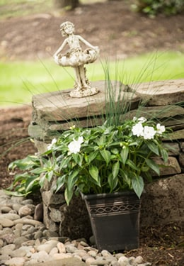 Garden stone wall with a little ballerina girl statue and a potted plant with white flowers.