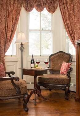 Two victorian style wingback chairs and a table with red wine, grapes and crackers.