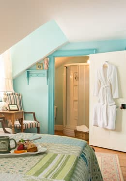 Breakfast tray on a neatly made bed facing the bathroom with a white robe hanging on the door.