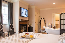View of the sleeping area and clawfoot tub near the fireplace and flatscreen tv.