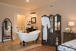 Bedroom with queen bed, clawfoot tub, hanging robe and soft lighting.