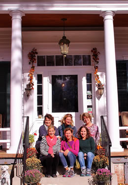 Group of six women sitting on the front porch staircase of the Inn.