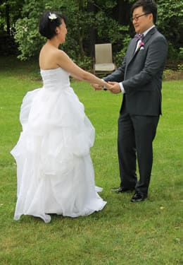 Bride and groom holding hands out on a grassy lawn, smiling at each other.
