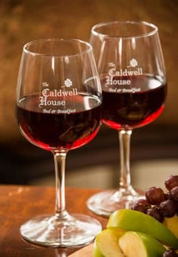 Two wine glasses with red wine in them and the Caldwell House logo embossed on them.