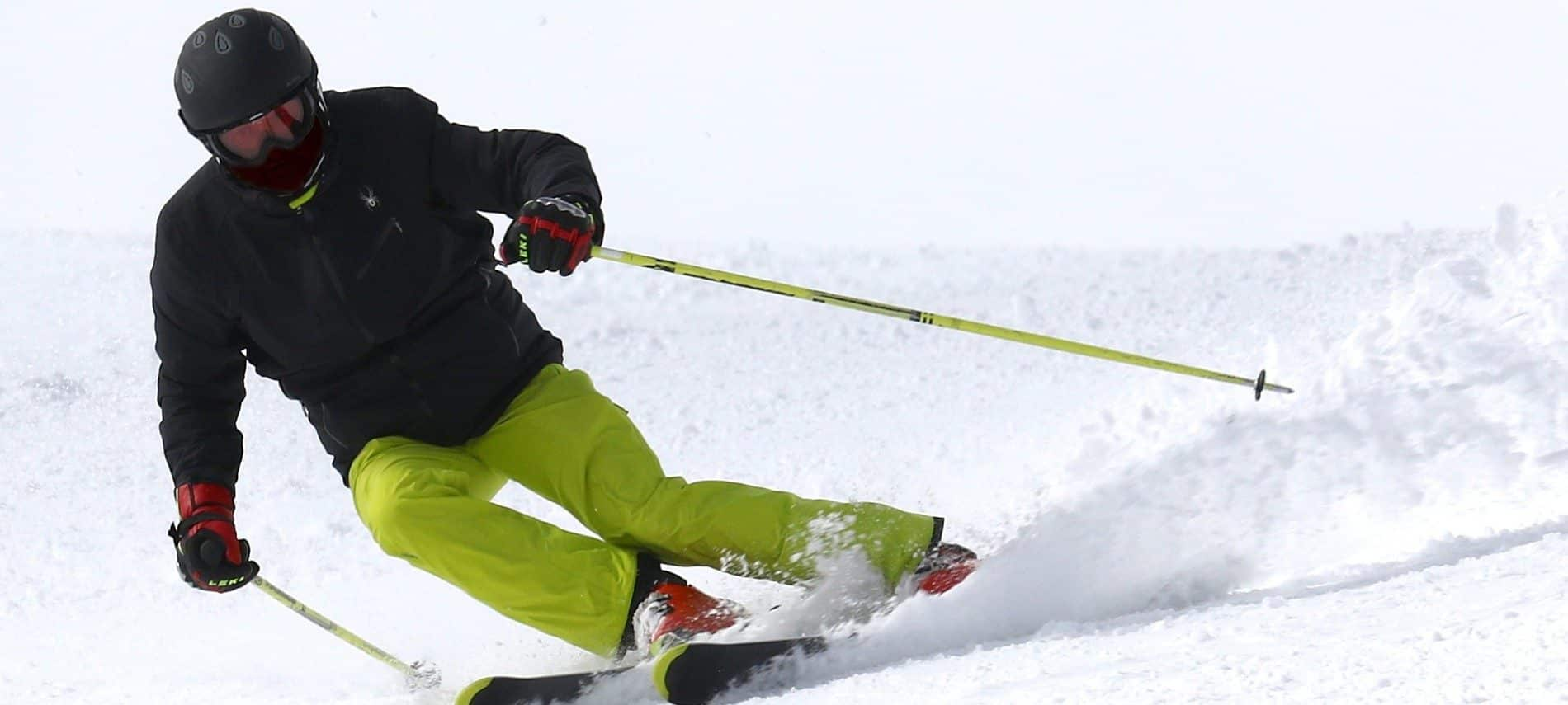 Man in black jacket and green snowpants on skis using poles to make a turn on a snow-covered hill