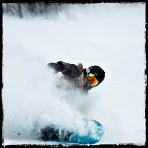 Male snowboarder coming down a ski hill with clouds of powdery snow all around