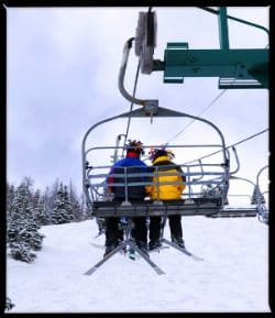 Two people on a ski lift together with snow all around