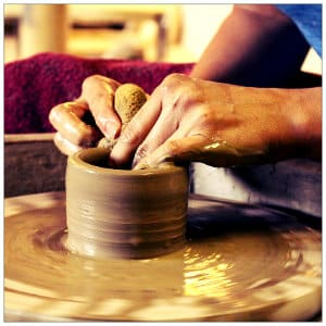 Person sitting at a pottery wheel with both hands on some clay making a bowl