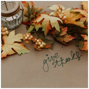 An assortment of dried yellow and orange leaves and berries on a table with brown paper with the words give thanks