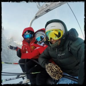 Three skiers in red and black coats and goggles sitting together on a chairlift with ski hill in background