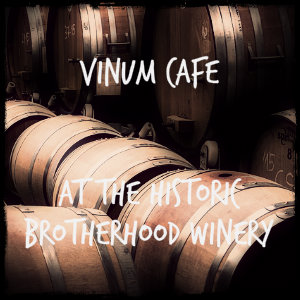 A number of brown wine barrels in a row with text Vinum Cafe at the Historic Brotherhood Winery