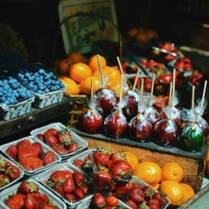 Colorful array of strawberries, blueberries, oranges, and candy apples at a vendor stall