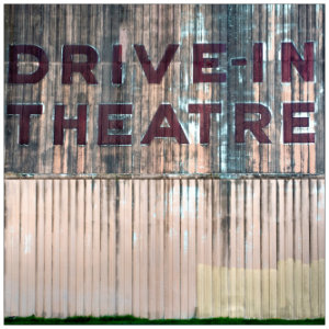 Old grey metal wall with text Drive In Theatre written in red