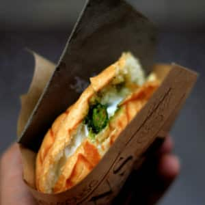 A hand holding a sandwich in brown paper from a food truck - image by lluis-domingo-30992 www.unsplash.com