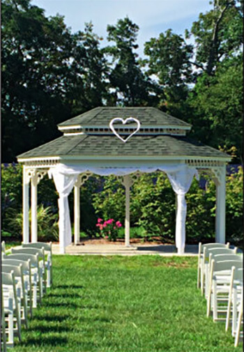 Small white wedding gazebo with green grass and several white chairs surrounding it.