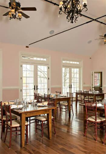 Dining room with hard wood floors and charming blush-colored walls; features numerous tables and large windows