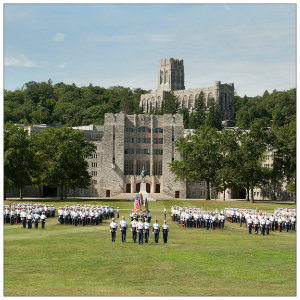 Large group of cadets in formation and dressed in white uniforms in front of a military academy