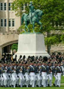Cadets in uniform walking across the grass with a giant statue of a man on a horse behind them