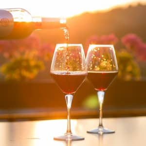 A person pouring red wine into two stemmed glasses on a table with bright sun in background