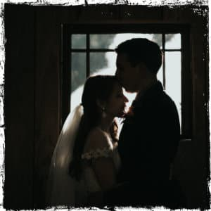 A young bride and groom standing in a dark dark in front of a window