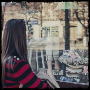 Woman in a black and red striped sweater looking into a window of a shop with women's clothing